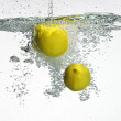 Fresh lemon dropped into water with splash isolated on white - Stock Photo