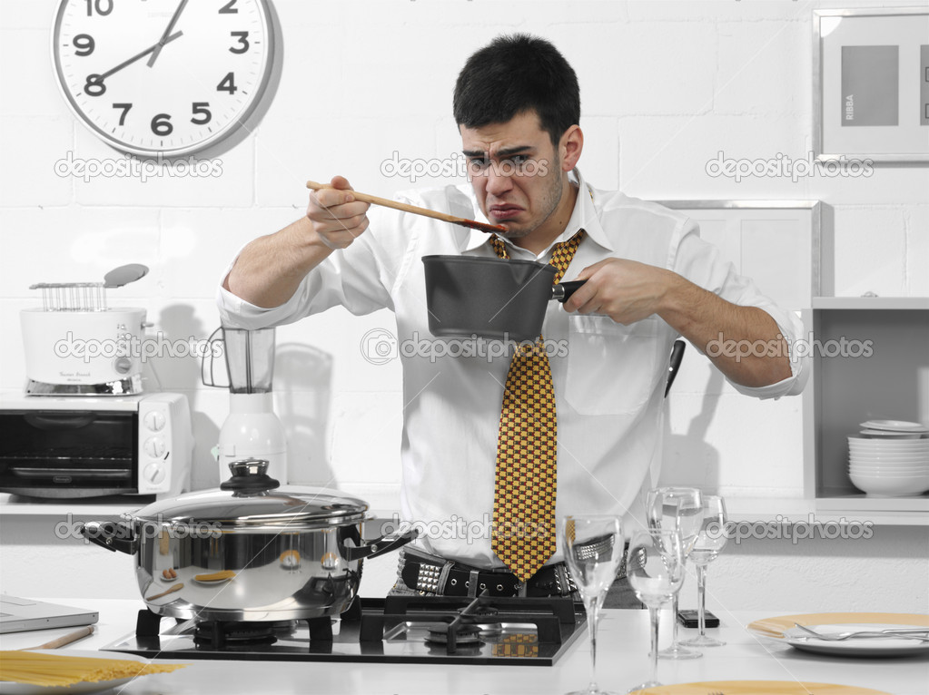 Business man in the kitchen that it tastes what he cooked — Stock Photo #11180312