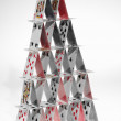Close up of house of playing cards on white background - Stock Photo