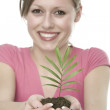 Beautiful blond girl holding young plant - Stock Photo