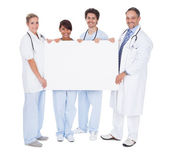 Group of doctors presenting empty board — Stock Photo