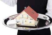 Close-up of a butler with model of a house — Stock Photo