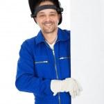 Confident welder presenting empty board — Stock Photo #10870316