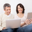 Mature couple using laptops in couch — Stock Photo