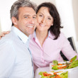 Mature couple having lunch at home - Stock Photo