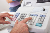 Sales person entering amount on cash register — Stockfoto