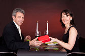 Man giving present to a woman in restaurant — Stock Photo