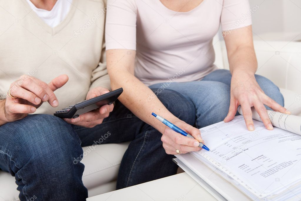Mature couple doing family finances at home — Stock Photo #10917771