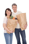 Happy couple with grocery shopping bags — Stok fotoğraf
