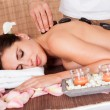 Beautiful young woman getting hot stone therapy — Stock Photo