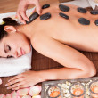 Beautiful young woman getting hot stone therapy - Stock Photo