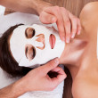 Beautiful young woman getting facial mask — Stock Photo