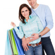 Beautiful young couple with shopping bags — Stock Photo