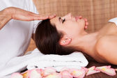 Beautiful young woman getting face massage — Stock Photo
