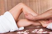 Beautiful young woman getting feet massage — Stock Photo