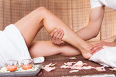 Beautiful young woman getting feet massage — Stock Photo