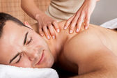 Young man getting shoulder massage — Stock Photo