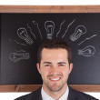 Businessman standing in front on blackboard — Stock Photo