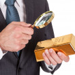 Businessman looking at gold bar through loupe — Stock Photo