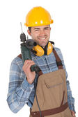 Worker holding drill and wearing hard hat — Stock Photo