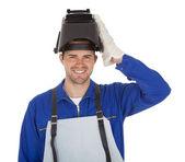 Trabalhador usando capacete e segurando a madeira — Foto Stock