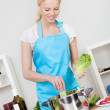 Cheerful young woman cooking - Stock Photo