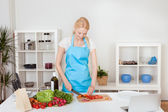 Cheerful young woman cooking — Stock Photo