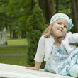Girl coquets on a bench - Stock Photo