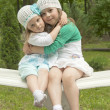 Sisters in park on a bench — Stock Photo