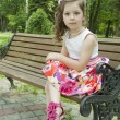 Sad girl sits in park on a bench — Stock Photo #11776345