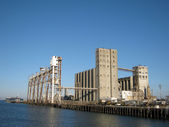 Large old rundown cement factory along the water — Stock Photo