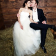 Couple in their wedding clothes in barn with hay - Stock Photo