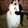 Couple in their wedding clothes in barn with hay — Stock Photo