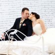 Bride and groom sitting on bed in bedroom - Stock Photo