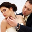 Groom kisses bride in white room — Stockfoto