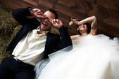 Couple in their wedding clothes in barn laughing — Stock Photo