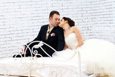 Bride and groom sitting on bed in bedroom — Stock Photo