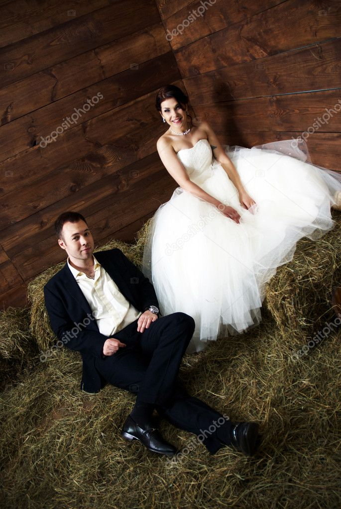 Couple in their wedding clothes in barn with hay fooling with each other — Stock Photo #11001249