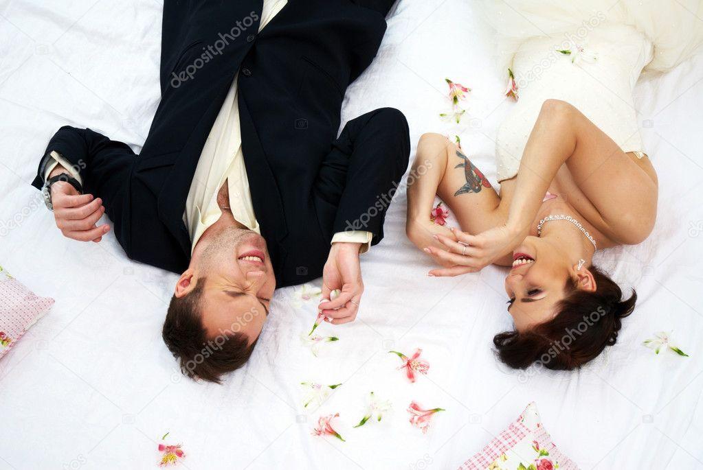 braut und bräutigam im schlafzimmer mit orchideen — stockfoto