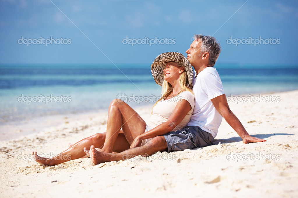 Full length of mature couple enjoying sunny day at beach — Stock fotografie #12149419