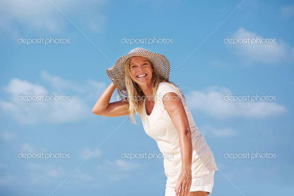 Portrait of relaxed mature woman enjoying in sun hat outdoors — Stock Photo #12149440