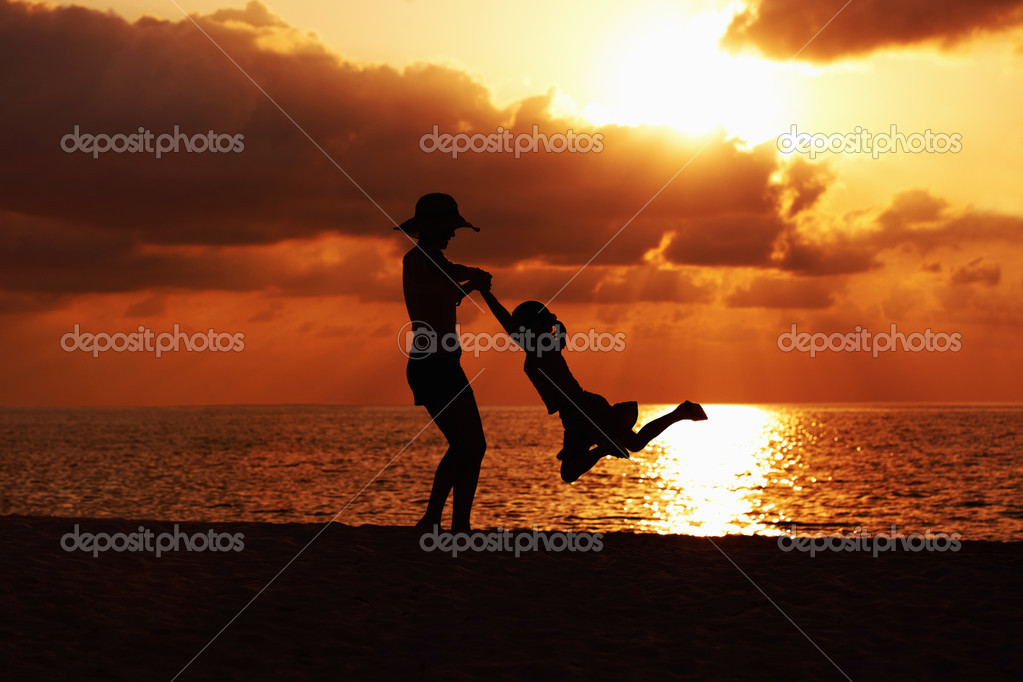 Silhouette of mother playing with her daughter on the beach at sunset  Stock Photo #12149552