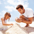 Family building sandcastles - Stockfoto