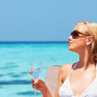 Beautiful woman relaxing at the seaside with a drink - Stock Photo