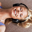 Beautiful girl enjoys listening music in headphones - Stok fotoraf