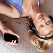 Beautiful woman at home listening music from cellphone - Stok fotoraf