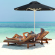 Couple relaxing on beach under umbrella - Foto Stock