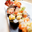 Different types of sushi served on wooden plate - Stock Photo
