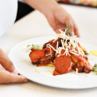 Chef hands serving a delicious dish - Stockfoto
