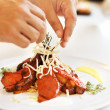Chef hands decorating delicious dish - Stockfoto